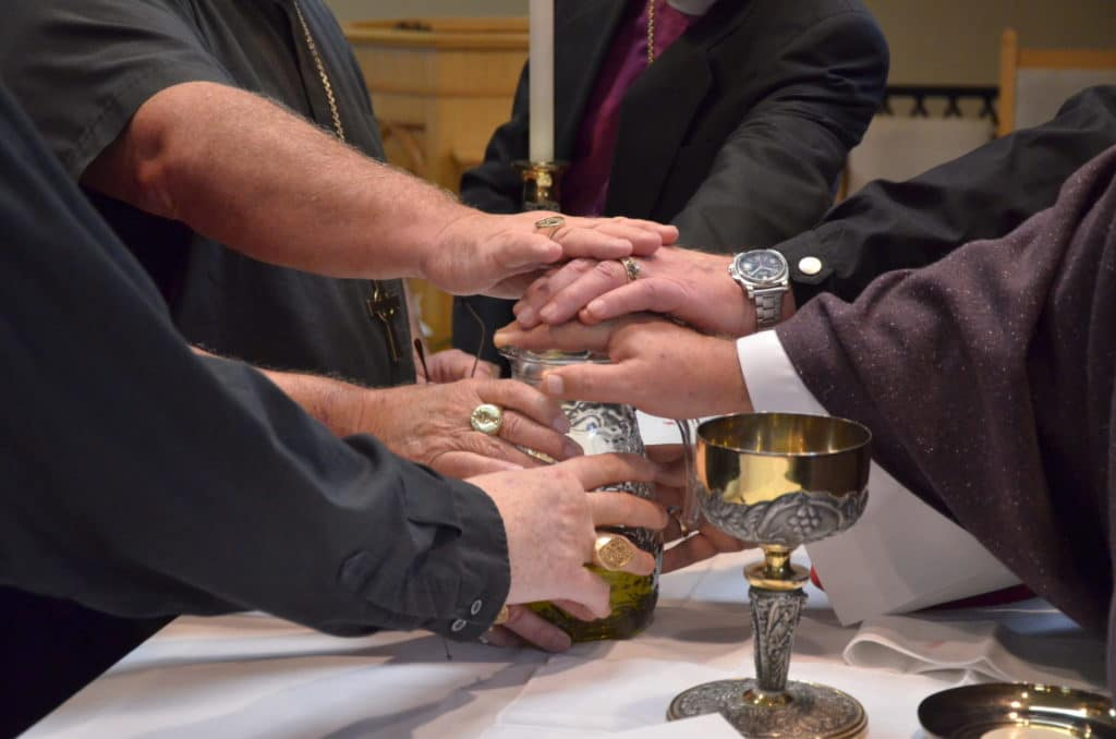 Laying Hands On The Chrism Oil